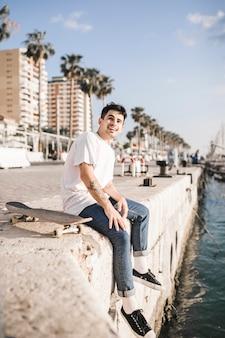 Retrato, de, um, feliz, homem jovem, com, um, skateboard