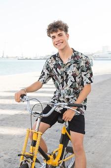 Retrato, de, um, feliz, homem jovem, sentando, ligado, bicicleta