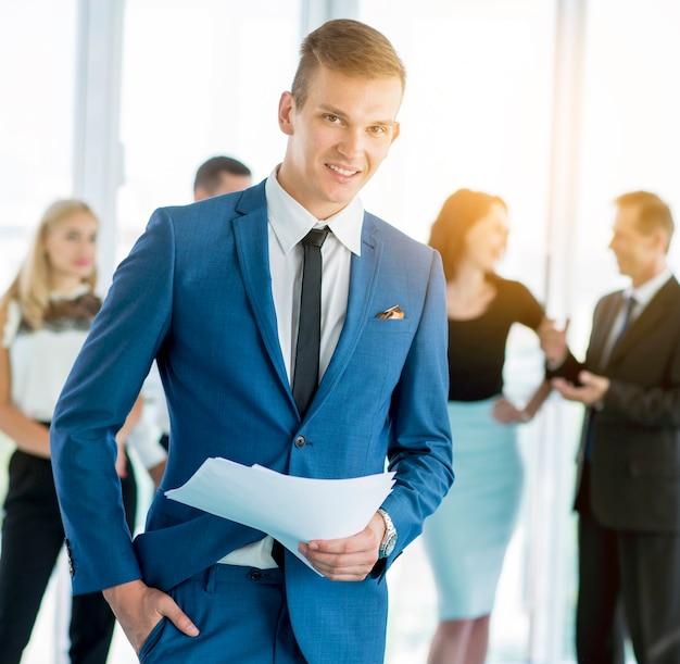 Retrato, de, um, feliz, homem negócios, segurando, documentos, com, colegas, em, fundo