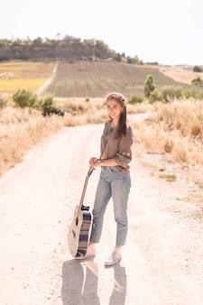 Retrato, de, um, feliz, menina adolescente, com, guitarra, ficar, ligado, trilha sujeira