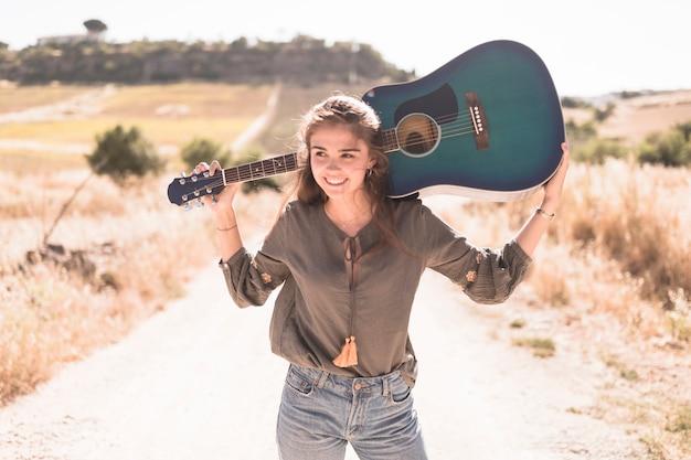 Retrato, de, um, feliz, menina adolescente, segurando, violão, ao ar livre