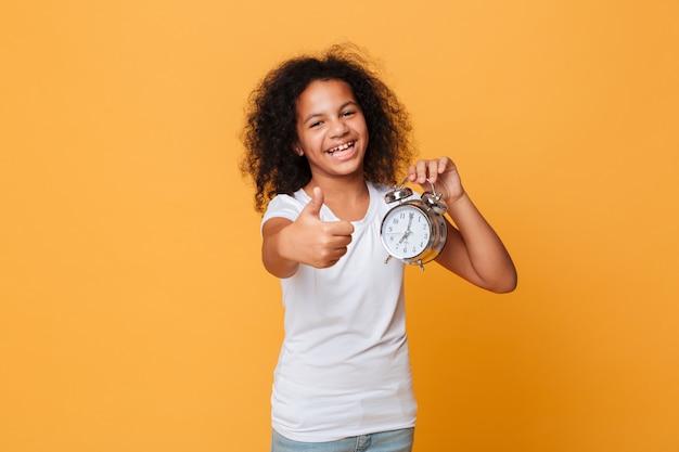 Retrato, de, um, feliz, menininha africana, segurando despertador
