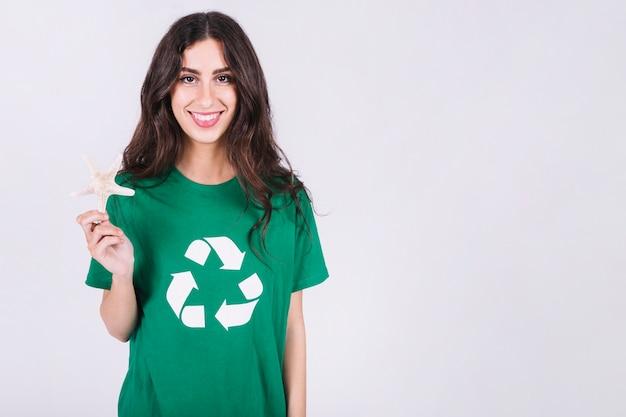 Retrato, de, um, feliz, mulher, em, verde, t-shirt, segurando, concha mar