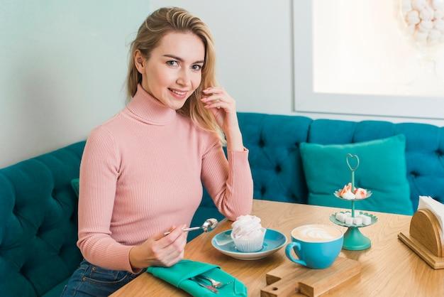Retrato, de, um, feliz, mulher jovem, com, merengue, e, café
