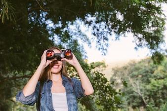 Retrato, de, um, feliz, mulher jovem, olhar através binóculos, em, floresta