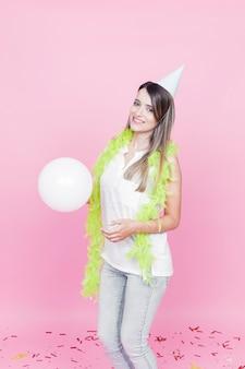 Retrato, de, um, feliz, mulher jovem, segurando, branca, balloon, ligado, cor-de-rosa, fundo