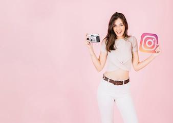 Retrato, de, um, feliz, mulher jovem, segurando, câmera, e, instagram, ícone