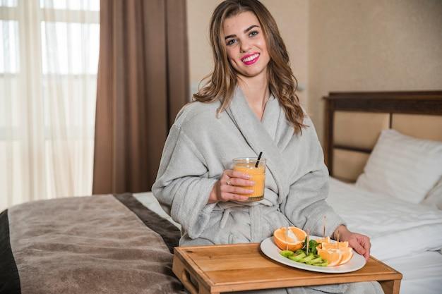 Retrato, de, um, feliz, mulher jovem, sentar-se cama, segurando, vidro suco, e, saudável, fatias, de, frutas, ligado, prato