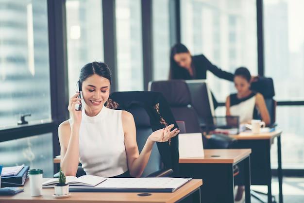 Retrato, de, um, feliz, mulher negócio, sentando, em, dela, local trabalho, em, escritório