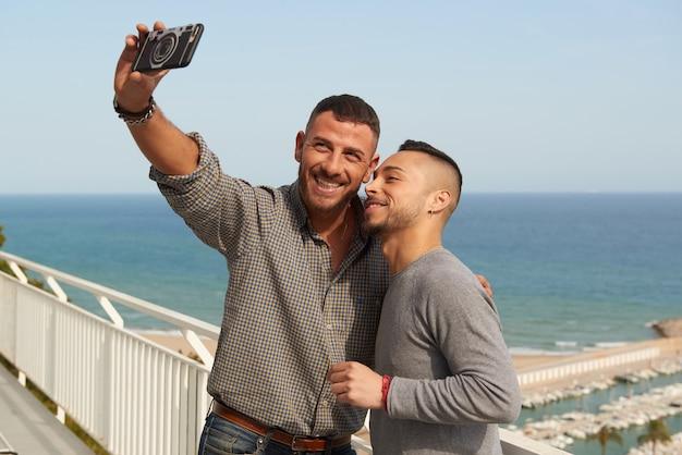 Retrato, de, um, feliz, par gay, ao ar livre, fazendo, um, selfie, com, seu, móvel