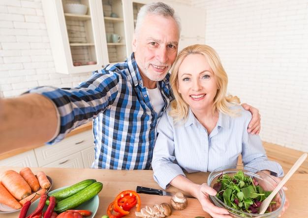 Retrato, de, um, feliz, par velho, levando, selfie, enquanto, preparar, salada, cozinha