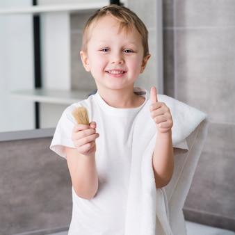 Retrato, de, um, feliz, pequeno menino, com, branca, toalha, sobre, seu, ombro, segurando, escova raspando, em, mão, mostrando, polegar, sinal