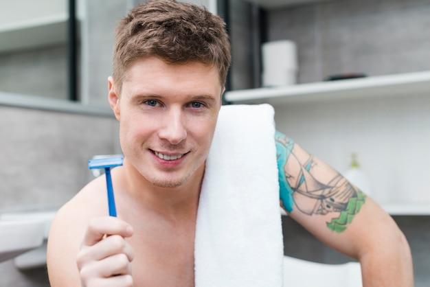 Retrato, de, um, feliz, shirtless, homem jovem, com, toalha, sobre, seu, ombro, segurando, azul, navalha, em, mão, olhando câmera