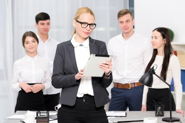 Retrato, de, um, femininas, gerente, segurando, tablete digital, em, mão, ficar, frente, colega