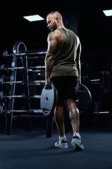 Retrato de um fisiculturista masculino tenso e tatuado segurando pesos nos braços
