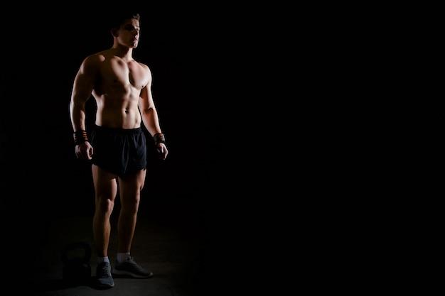Retrato de um fisiculturista musculoso bonito com torso muscular no ginásio.