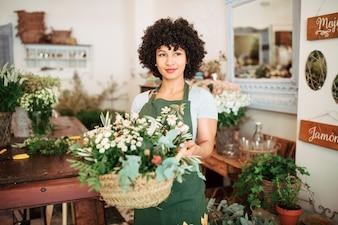 Retrato, de, um, florista feminino, segurando, cesta, de, flores frescas