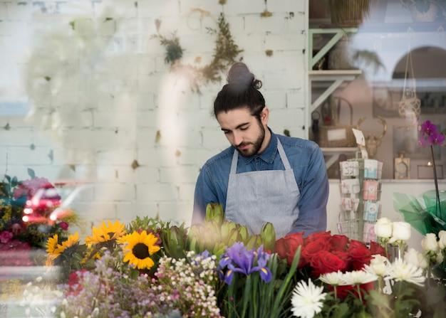 Retrato de um florista masculino em pé atrás das flores coloridas na loja de flores