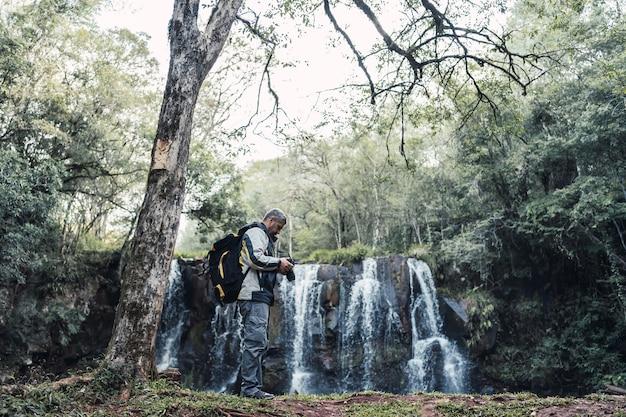 Retrato de um fotógrafo do sexo masculino com um fundo de cachoeira.