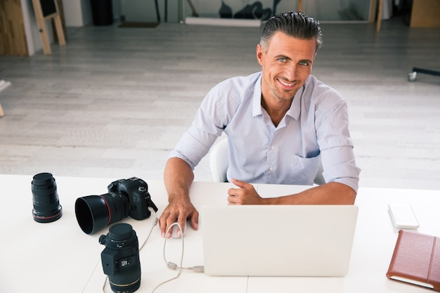 Retrato de um fotógrafo feliz usando laptop em seu local de trabalho