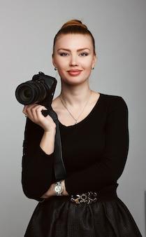 Retrato de um fotógrafo jovem e bonita com sua câmera. fotografia de estúdio. sessão de fotos