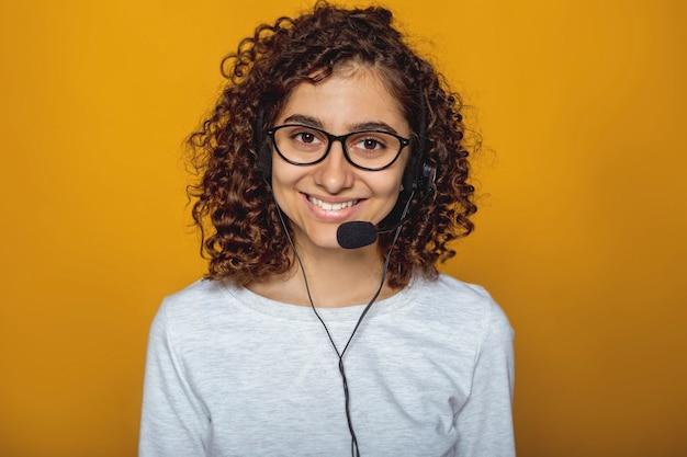 Retrato de um funcionário do centro de chamada garota feliz em fones de ouvido e óculos.