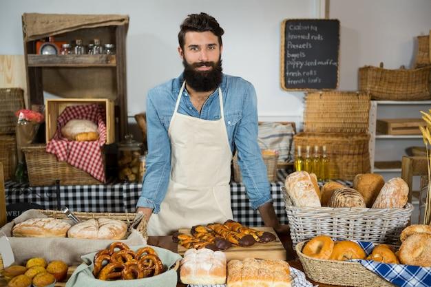 Retrato de um funcionário do sexo masculino em pé no balcão da padaria