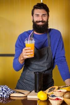 Retrato de um funcionário masculino segurando um copo de suco