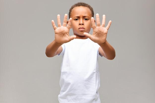 Retrato de um garotinho afro-americano sério vestido com uma camiseta branca, carrancudo e com uma expressão facial mal-humorada, mostrando todos os dez dedos em ambas as mãos fazendo nenhum gesto ou sinal de stop