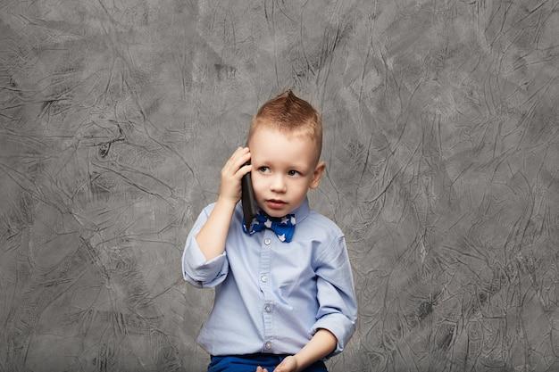Retrato de um garotinho fofo com camisa azul e gravata borboleta com telefone celular contra textura cinza