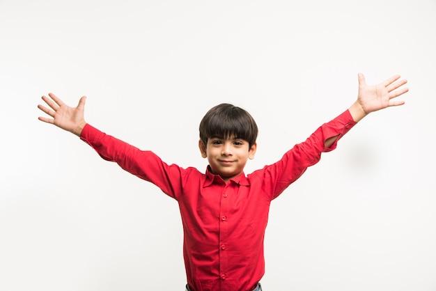 Retrato de um garotinho indiano asiático fofo de camisa vermelha com as mãos estendidas ou dobradas Foto Premium