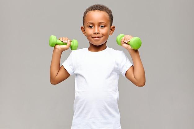 Retrato de um garoto afro-americano alegre com braços magros, sorrindo alegremente durante o exercício no ginásio com dois halteres, vai construir um corpo atlético saudável e forte. fitness e crianças