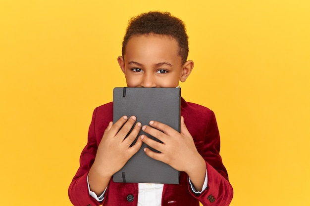 Retrato de um garoto afro-americano bonito, com olhos brincalhões, cobrindo o rosto com o livro preto. pupila negra posando isolada segurando o diário, mantendo o segredo