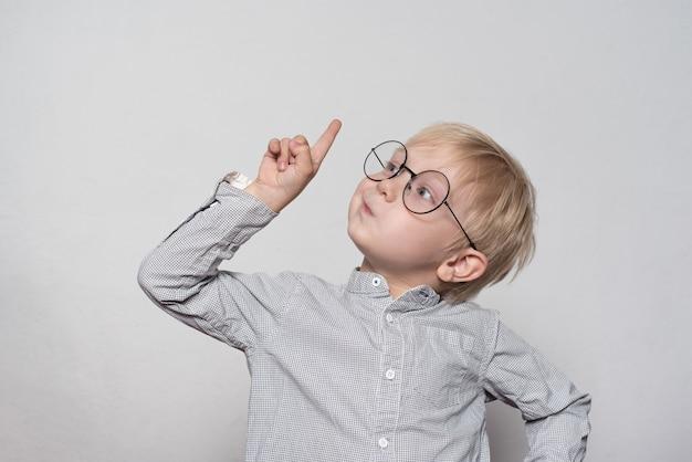 Retrato de um garoto loiro bonito com óculos grandes. dedo apontando para cima.