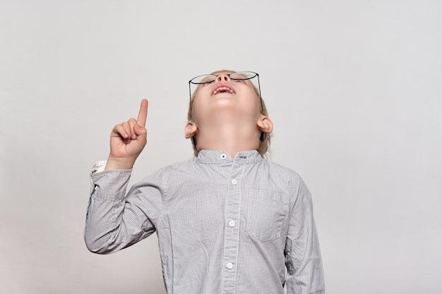 Retrato de um garoto loiro bonito com óculos grandes. ele olha para cima e aponta um dedo. fundo branco.