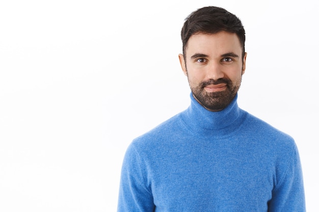 Retrato de um gerente, chefe ou funcionário confiante e profissional do sexo masculino com barba, sorrindo satisfeito, sentindo-se bem-sucedido e seguro de si, assertivo, de pé na parede branca