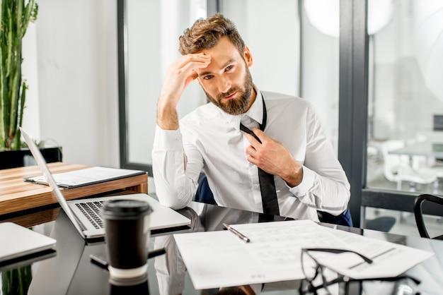 Retrato de um gerente fiscal cansado tirando uma gravata enquanto trabalhava com documentos fiscais e laptop no escritório