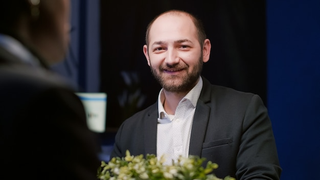 Retrato de um gerente focado, olhando para a câmera, sentado à mesa de conferência no escritório de reuniões