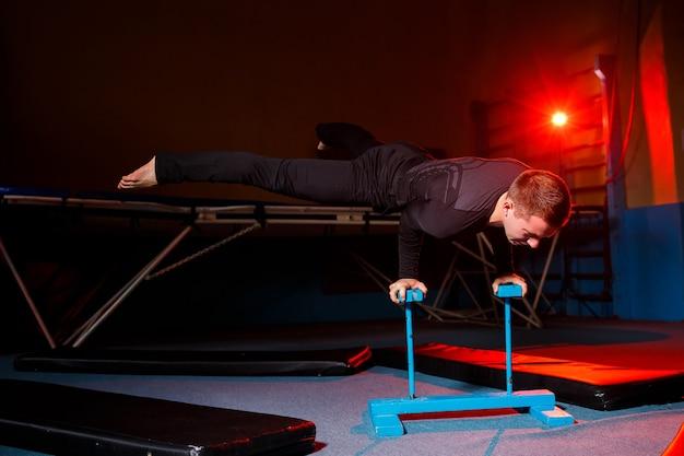 Retrato de um ginasta em roupas esportivas, homem fazendo exercícios em um cavalo na academia