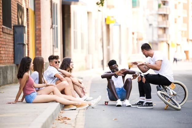 Retrato de um grupo de amigos jovens hippie conversando em uma área urbana.