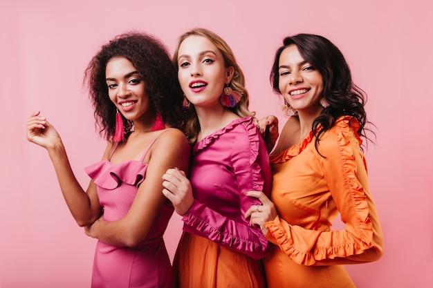 Retrato de um grupo de amigos sorrindo na parede rosa