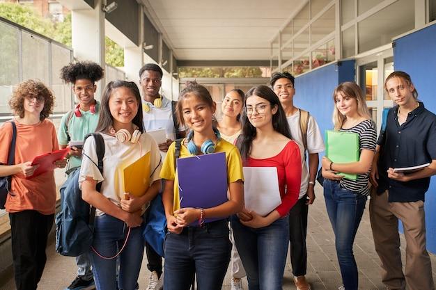 Retrato de um grupo de estudantes, olhando para a câmera, jovens de diferentes etnias posando ...