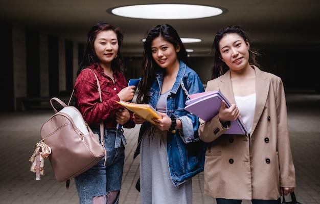 Retrato de um grupo de garotas asiáticas curtindo o tempo juntas no campus da faculdade