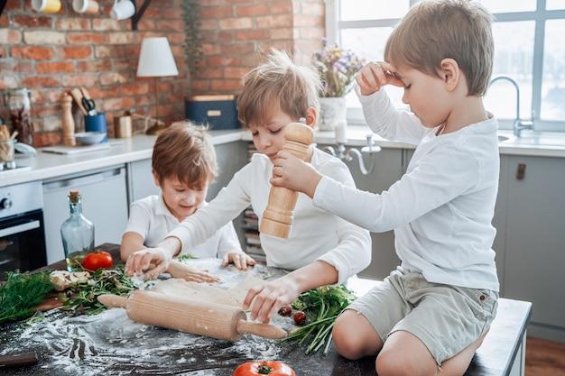 Retrato de um grupo de três meninos vestidos com camisas brancas e shorts que aprendem a cozinhar e se divertir na cozinha.