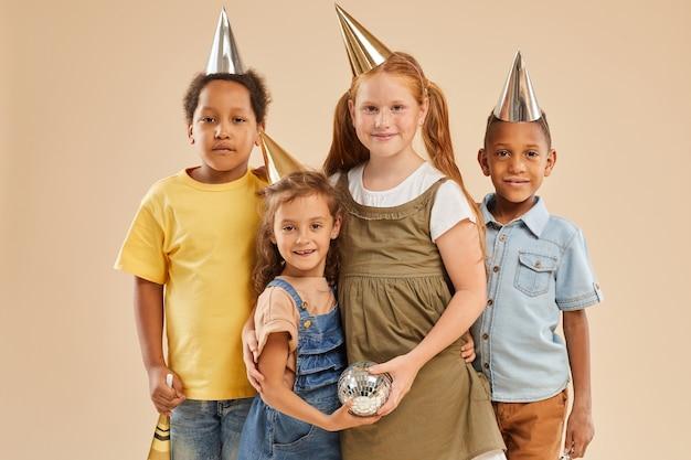 Retrato de um grupo diversificado de crianças com chapéus de festa posando em bege