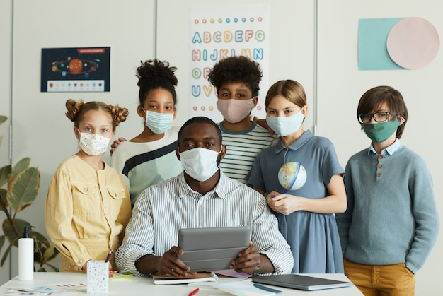 Retrato de um grupo diversificado de crianças com um professor usando máscaras na escola e olhando para a câmera, medidas de segurança ambíguas