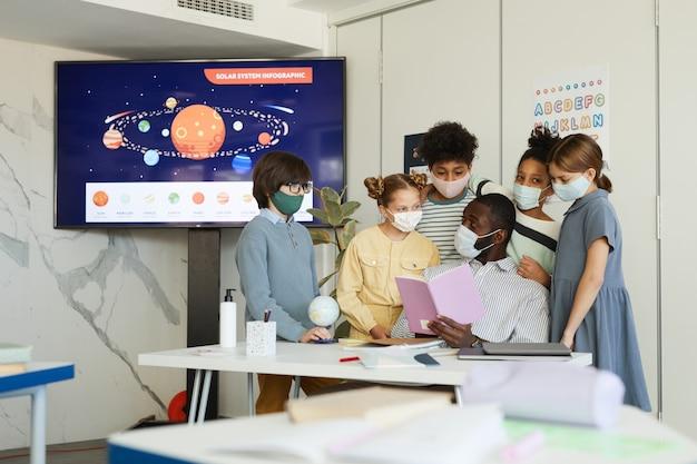 Retrato de um grupo diversificado de crianças e professores usando máscaras na sala de aula da escola, medidas de segurança ambiciosas, copie o espaço