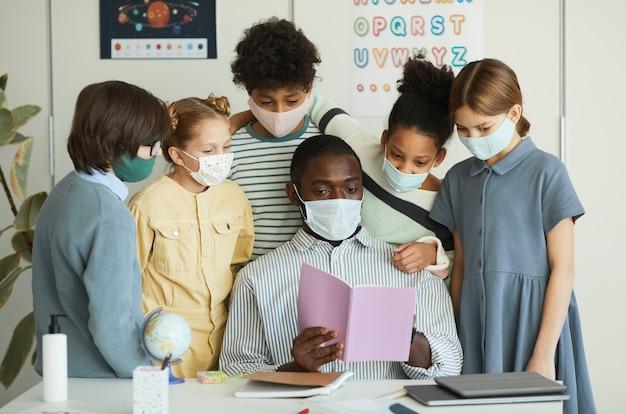 Retrato de um grupo diversificado de crianças e professores usando máscaras na sala de aula da escola, medidas de segurança ambiciosas