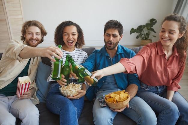 Retrato de um grupo multiétnico de amigos assistindo tv juntos, sentados em um sofá confortável em casa e tocando garrafas de cerveja