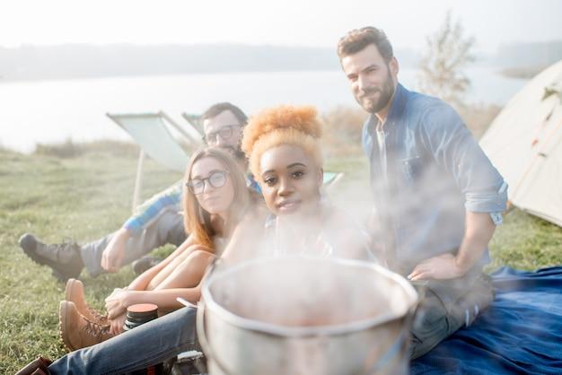 Retrato de um grupo multiétnico de amigos durante o piquenique com a panela e o vapor no acampamento